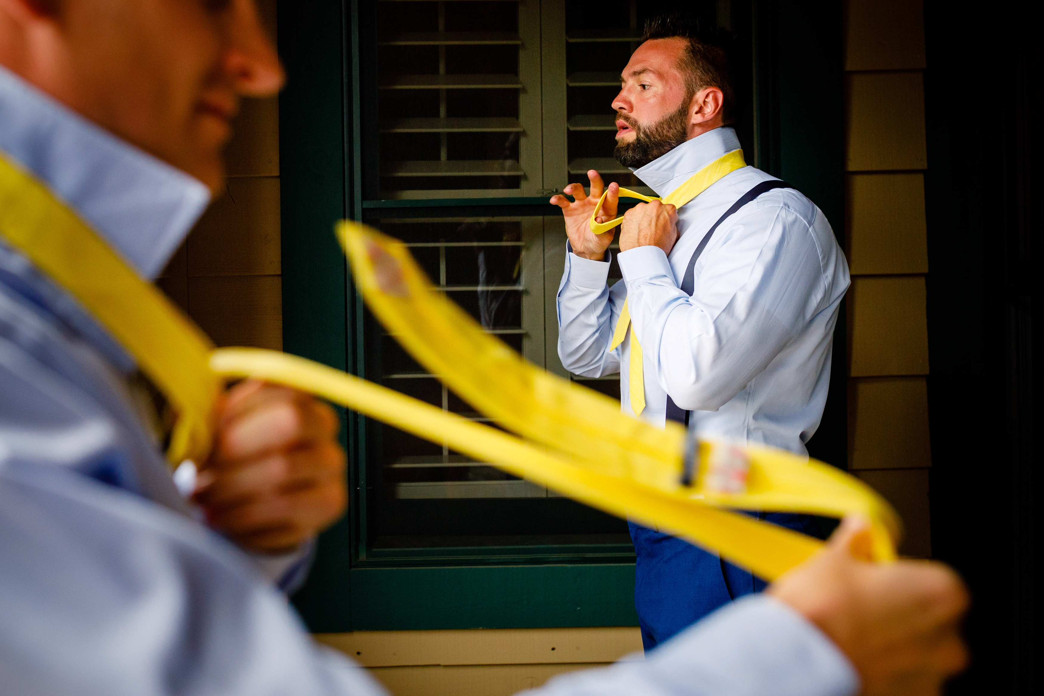 Groom putting on tie at Keystone for Mountain Wedding