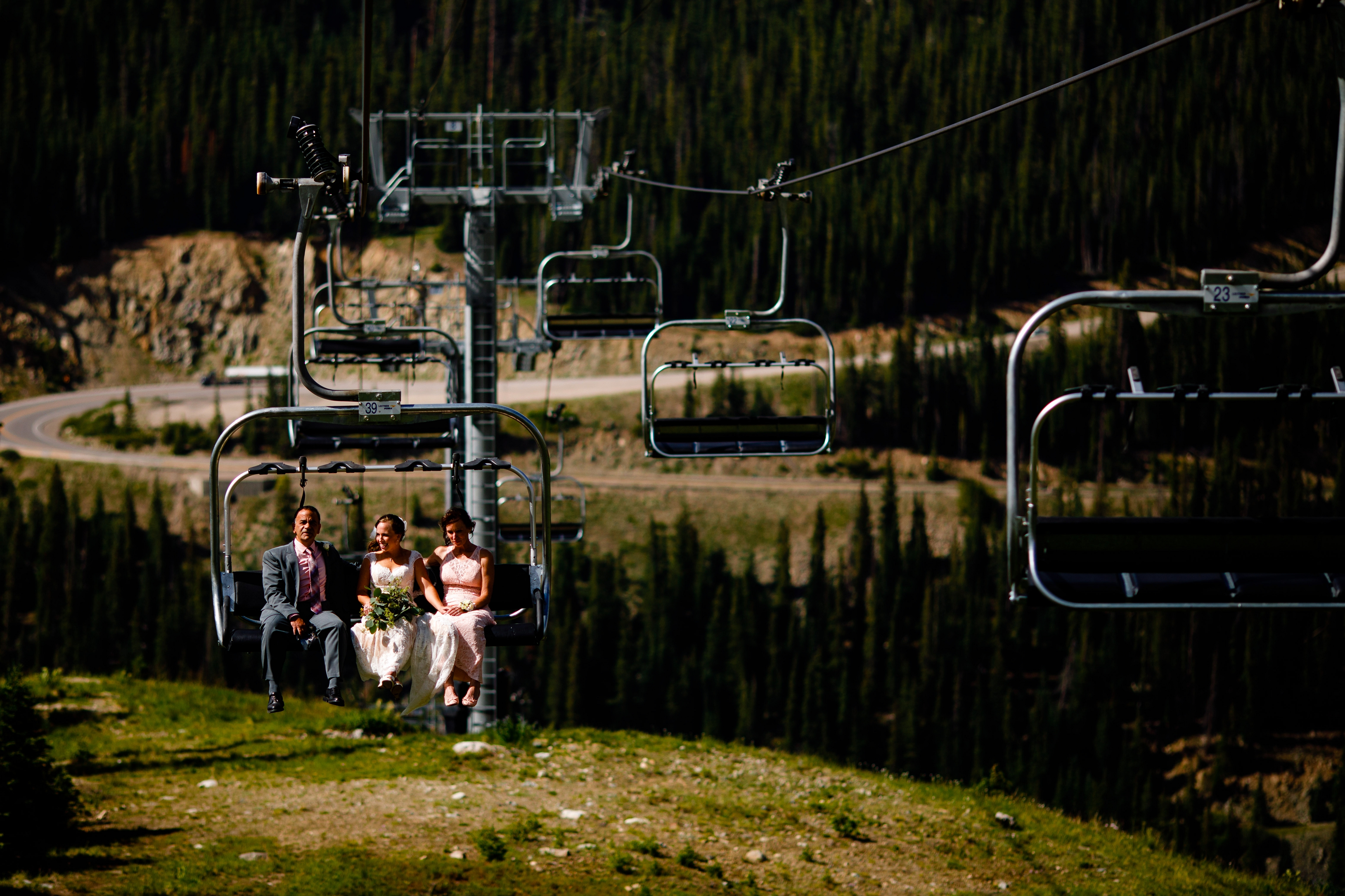 Bride riding the chairlift with her parents before walking down the isle to get married.