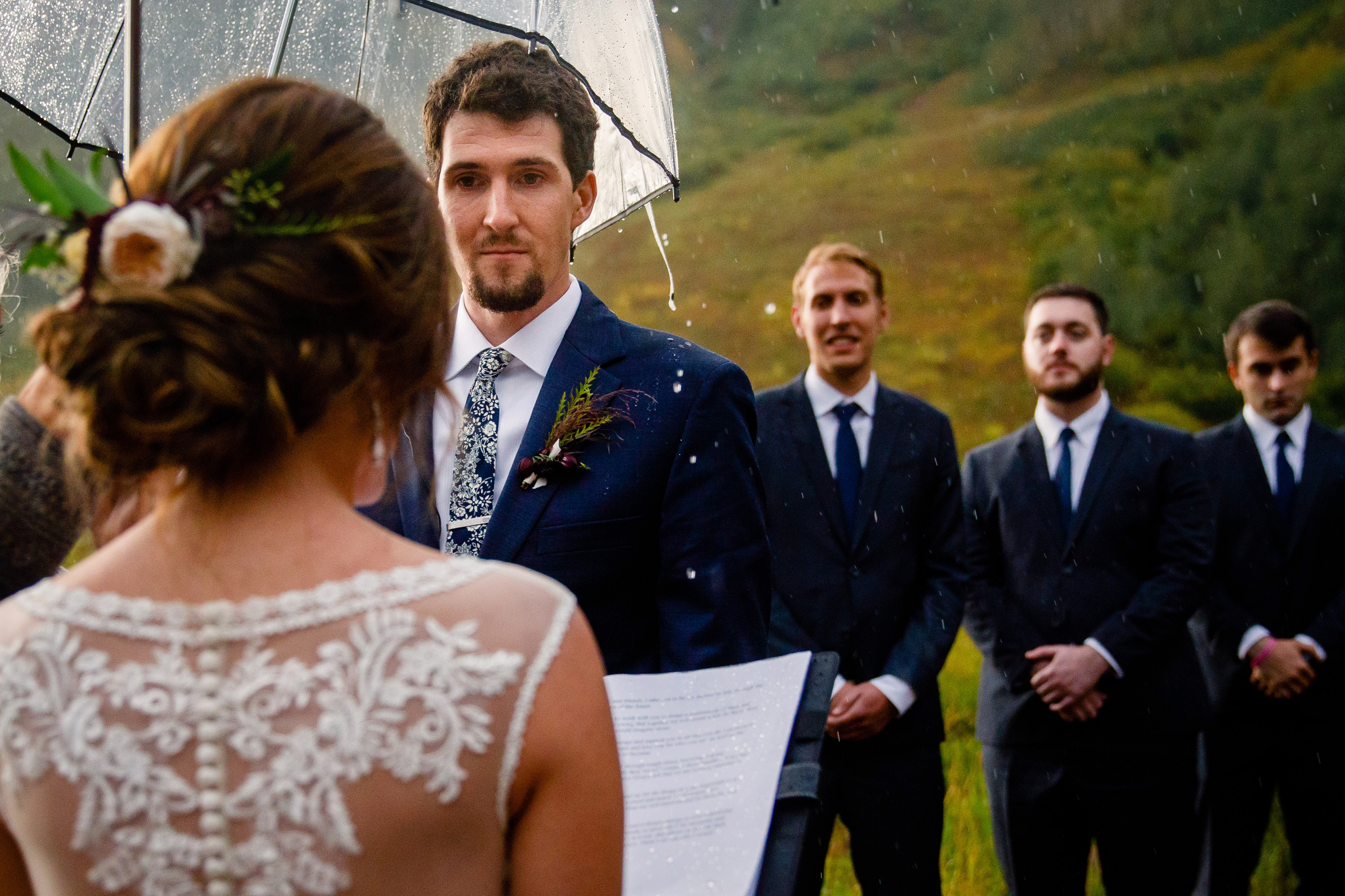 Rain pouring off the umbrella as a bride reads her vows at the Maroon Bells.