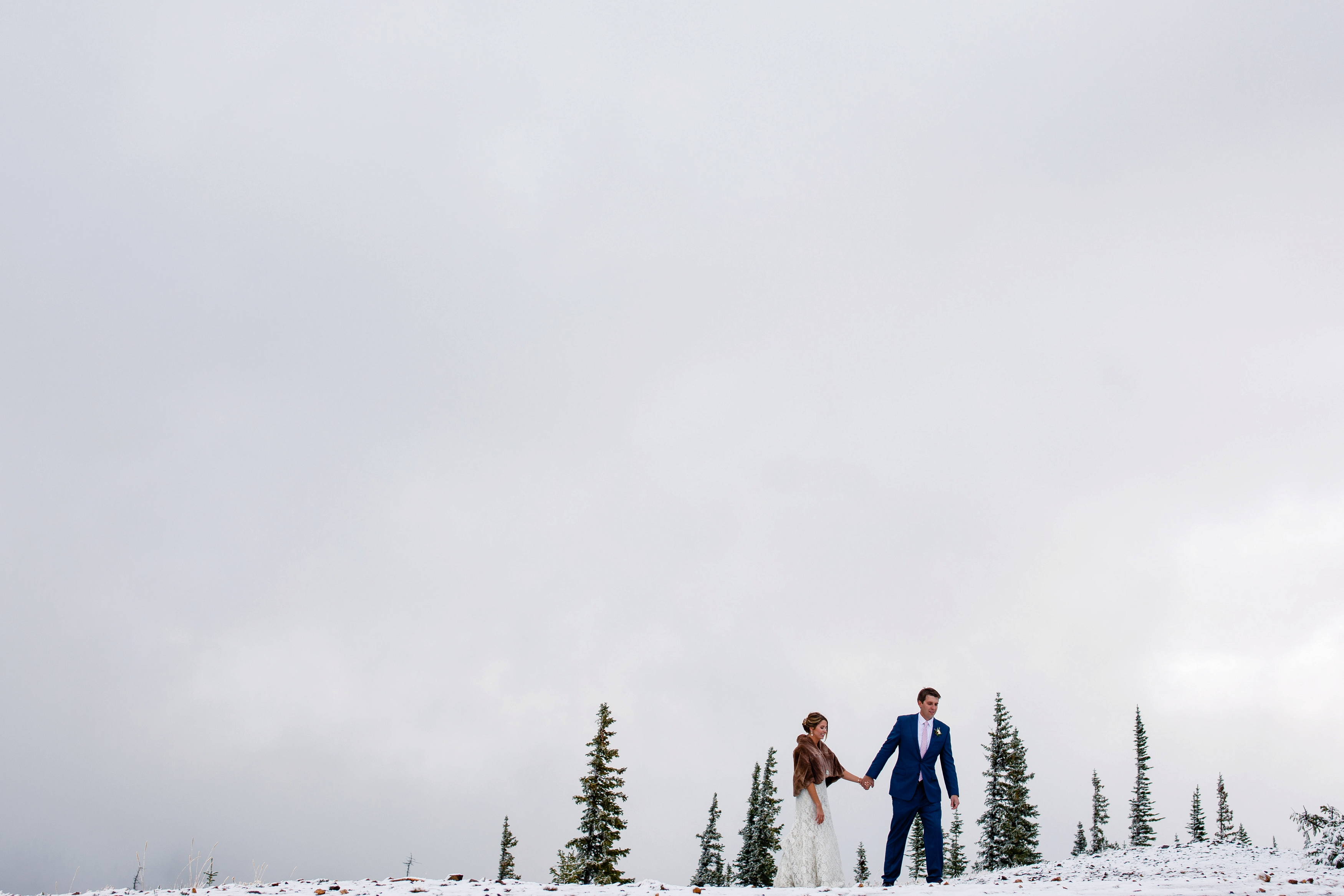 A bride & groom walk in the snow for their portraits during their Tenmile Station Fall Wedding.