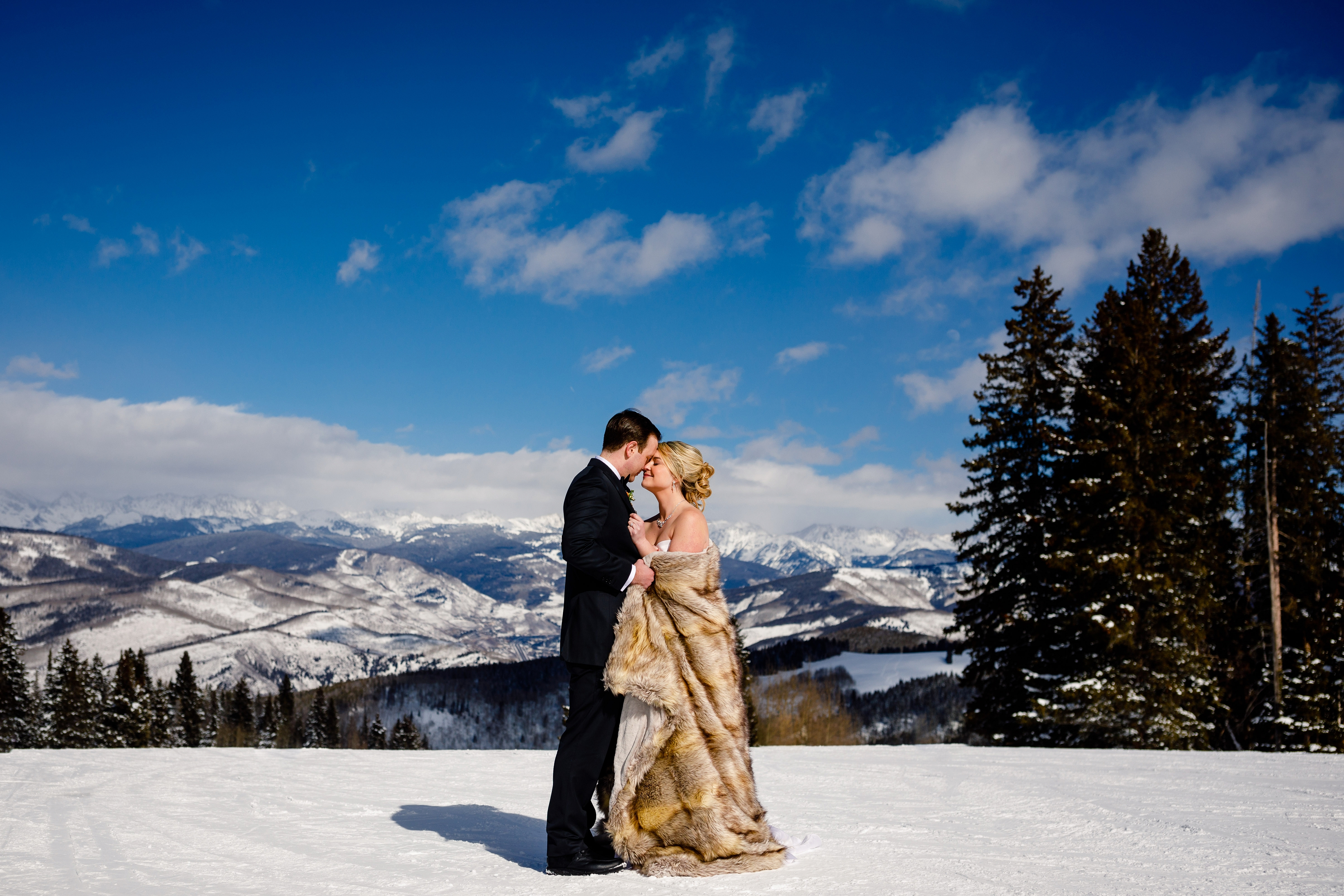 A beautiful wedding couple pose for a portrait on top of Beaver Creek Resort before their ceremony.
