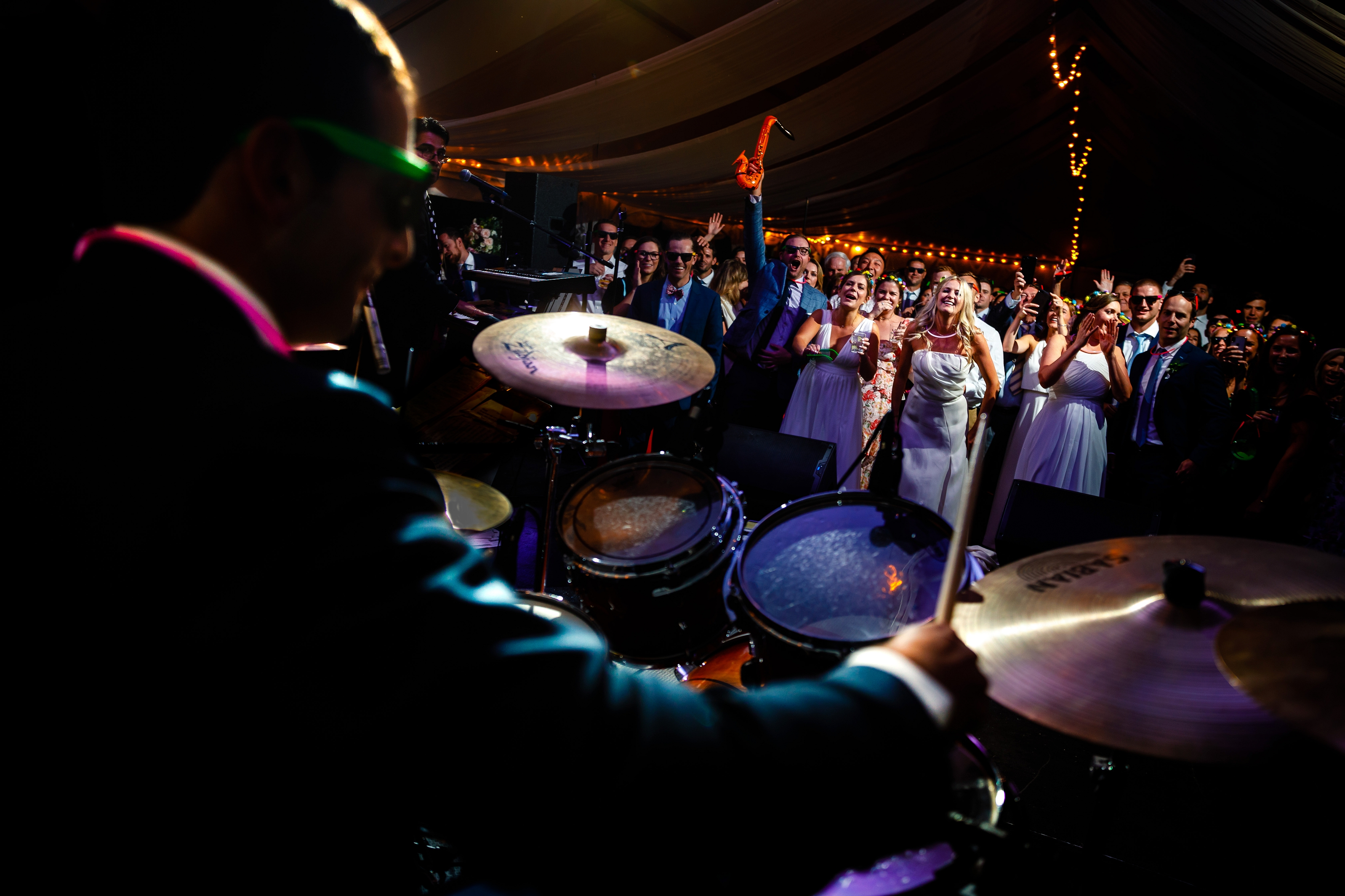 Groom playing the drums during the wedding reception at Camp Hale in Red Cliff, CO.