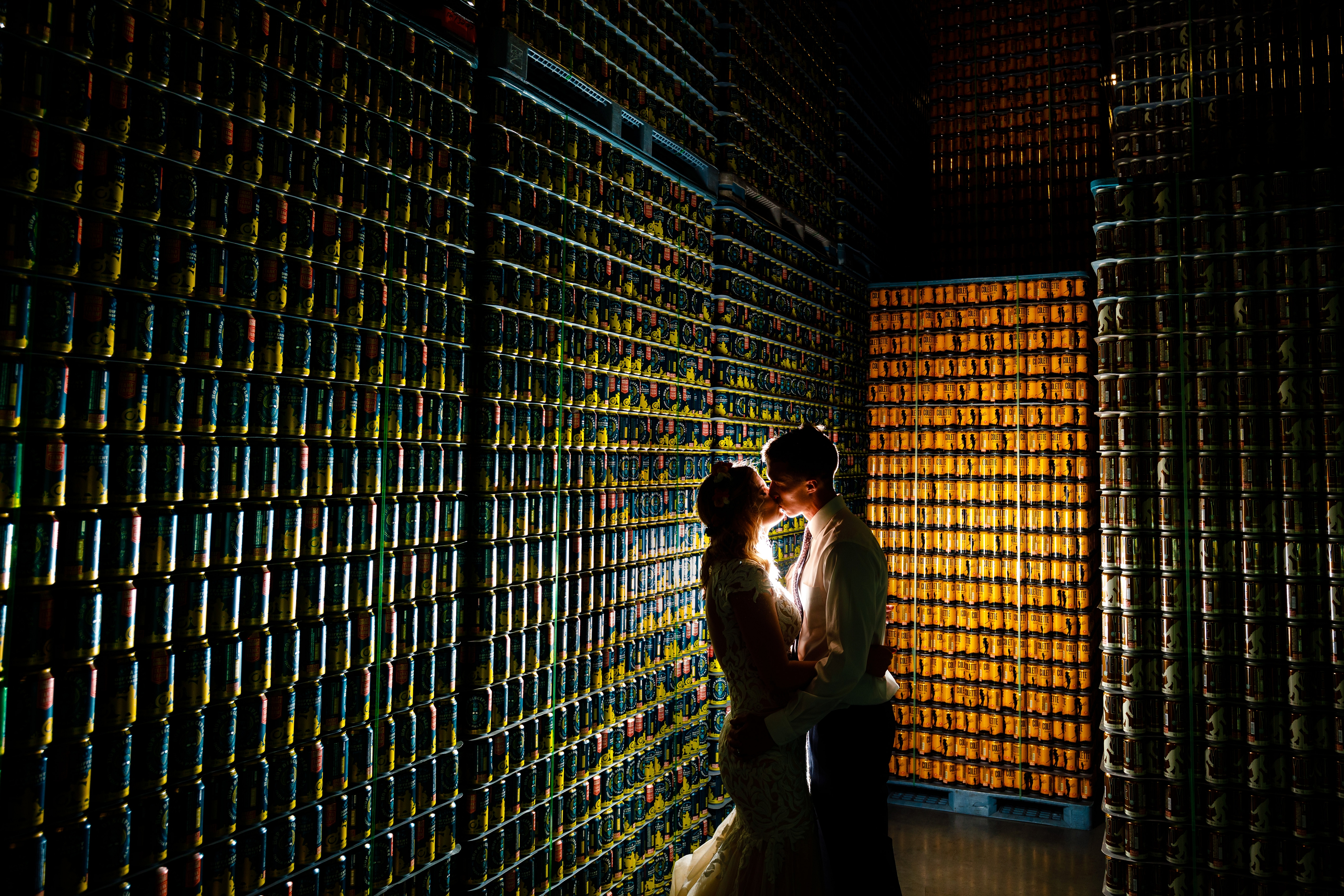 A nightcap portrait of Jake & Jessica in front of thousands of Great Divide beer cans during their wedding reception at Great Divide Brewery.
